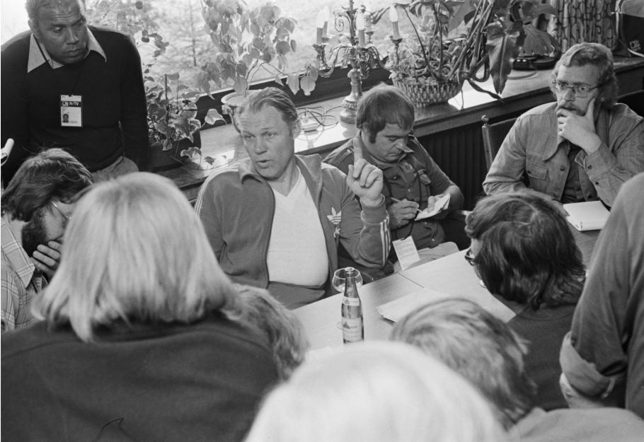 De Dode van de Week, Hugo Walker (linksboven), luistert met collega-journalisten naar Rinus Michels tijdens het WK van 1974 in Duitsland (Foto: Anefo / Bert Verhoef)